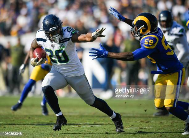 Running back Rashaad Penny of the Seattle Seahawks gets around inside linebacker Cory Littleton of the Los Angeles Rams to score a touchdown in the...