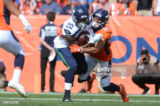 Running back Rashaad Penny of the Seattle Seahawks is tackled by defensive back Justin Simmons of the Denver Broncos at Broncos Stadium at Mile High...
