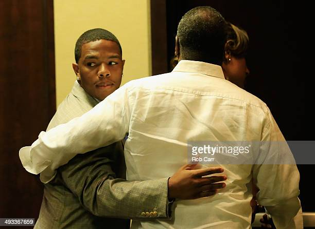 Running back Ray Rice of the Baltimore Ravens gets a hug from his wife Janay and father in law Joe Palmer following a news conference at the Ravens...