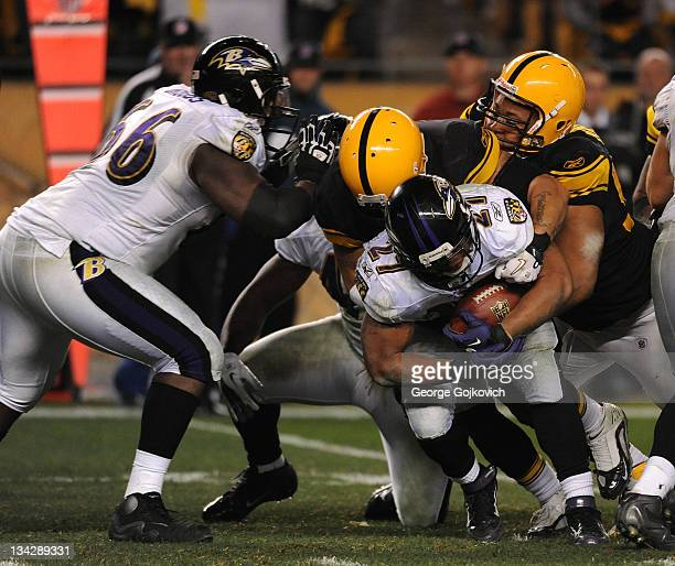 Running back Ray Rice of the Baltimore Ravens is tackled by linebacker Larry Foote and defensive lineman Casey Hampton of the Pittsburgh Steelers...