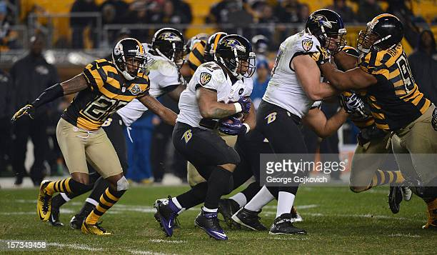 Running back Ray Rice of the Baltimore Ravens runs with the football as he is pursued by cornerback Keenan Lewis of the Pittsburgh Steelers and as...