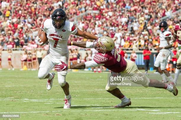 Running back Reggie Bonnafon of the Louisville Cardinals looks to maneuver by defensive back Derwin James of the Florida State Seminoles at Doak...
