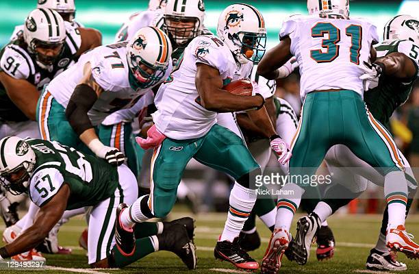 Running back Reggie Bush of the Miami Dolphins runs the ball against the New York Jets at MetLife Stadium on October 17 2011 in East Rutherford New...