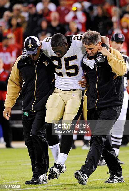 Running back Reggie Bush of the New Orleans Saints after hurting his knee against the San Francisco 49ers is carried off the field during an NFL...