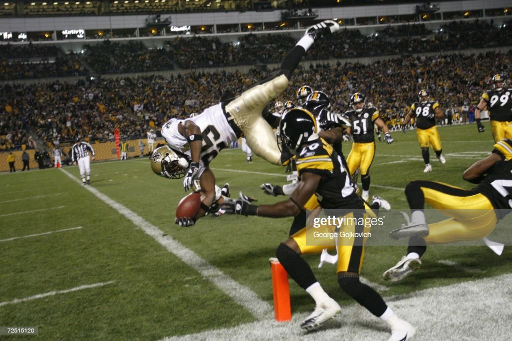 Running back Reggie Bush #25 of the New Orleans Saints scores on a 15-yard touchdown run against defensive backs Tyrone Carter #23 and Bryant McFadden #20 of the Pittsburgh Steelers at Heinz Field on November 12, 2006 in Pittsburgh, Pennsylvania. The Steelers defeated the Saints 38-31.
