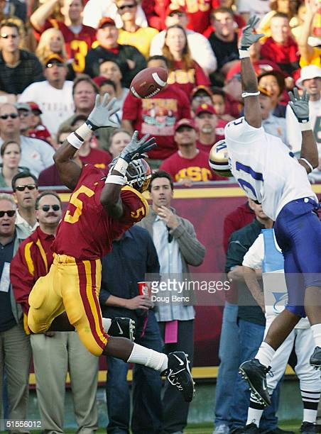 Running back Reggie Bush of the USC Trojans catches a touchdown pass in the second quarter as cornerback Derrick Johnson of the Washington Huskies...