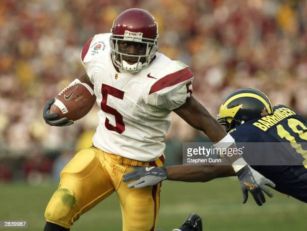 Running back Reggie Bush of the USC Trojans runs arouund safety Willlis Barringer of the Michigan Wolverines during the 2004 Rose Bowl on January 1,...