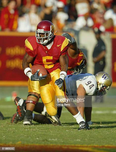 Running back Reggie Bush of the USC Trojans runs upfield against the Washington Huskies at the Los Angeles Coliseum on October 23, 2004 in Los...