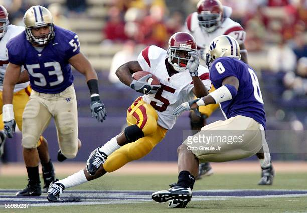 Running back Reggie Bush of the USC Trojans rushes against Joe Lobendahn and Dashon Goldson of the Washington Huskies in the first half on October 22...