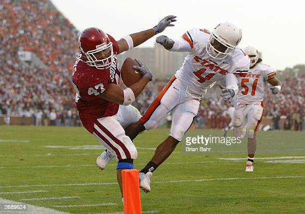 Running back Renaldo Works of the Oklahoma Sooners gets knocked out of bounds on the one yard line by cornerback Daniel McLemore of the Oklahoma...