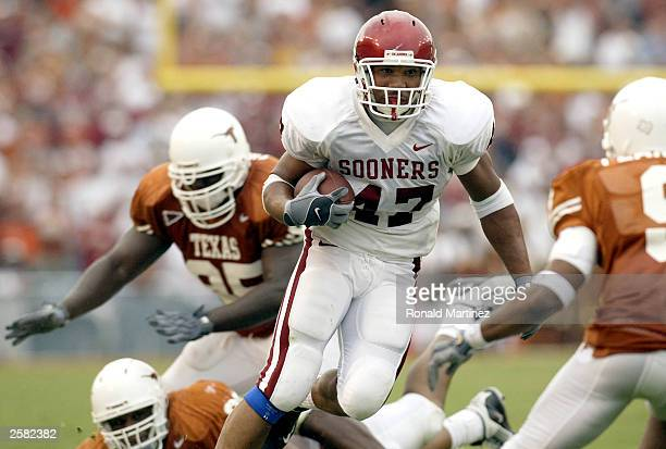 Running back Renaldo Works of the Oklahoma Sooners runs for a first down against the Texas Longhorns defense at the Cotton Bowl on October 11 2003 in...
