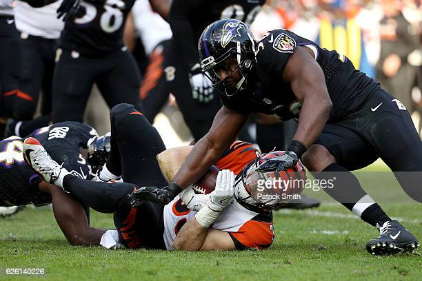 Running back Rex Burkhead of the Cincinnati Bengals is tackled by outside linebacker Albert McClellan and inside linebacker Zach Orr of the Baltimore...