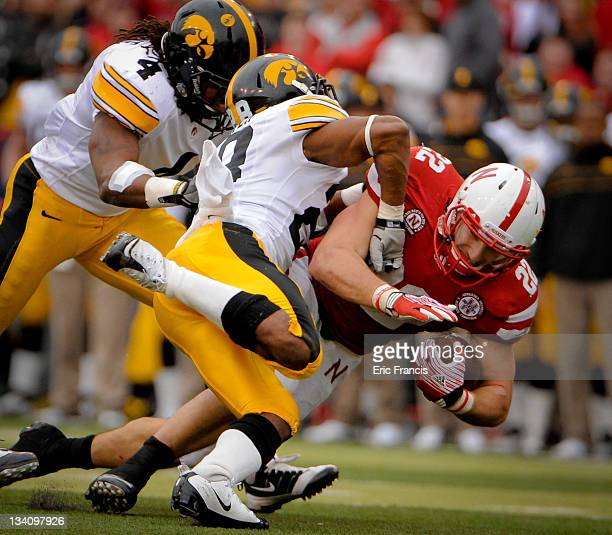 Running back Rex Burkhead of the Nebraska Cornhuskers is brought down by defensive back Shaun Prater and defensive back Jordan Bernstine of the Iowa...