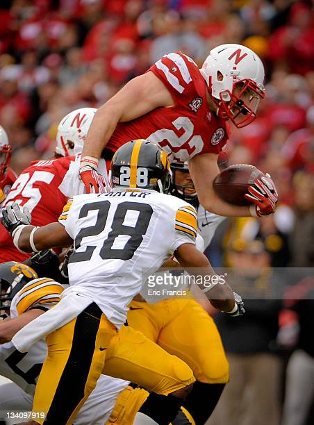 Running back Rex Burkhead of the Nebraska Cornhuskers leaps high over defensive back Shaun Prater and the the Iowa Hawkeyes' defense during their...