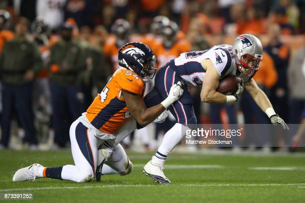 Running back Rex Burkhead of the New England Patriots is tackled after a catch by inside linebacker Brandon Marshall of the Denver Broncos in the...