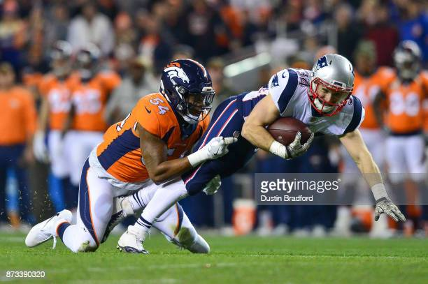 Running back Rex Burkhead of the New England Patriots is tackled by inside linebacker Brandon Marshall of the Denver Broncos after a catch in the...