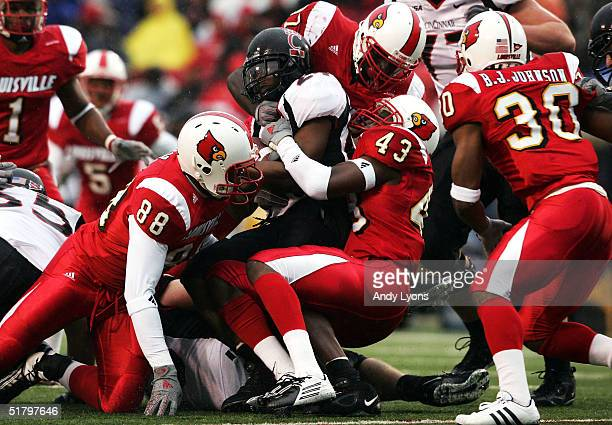Running back Richard Hall of the Cincinnati Bearcats is tackled by safety Abe Brown, defensive end Brandon Cox and linebacker Brandon Johnson of the...