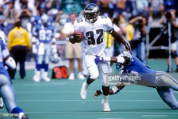 Running Back Ricky Watters of the Philadelphia Eagles tries to break the tackle of Bennie Blades of the Detroit Lions during an NFL football game...