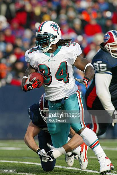 Running back Ricky Williams of the Miami Dolphins attempts to break free from a Buffalo Bills defender during the game on December 21, 2003 at Ralph...