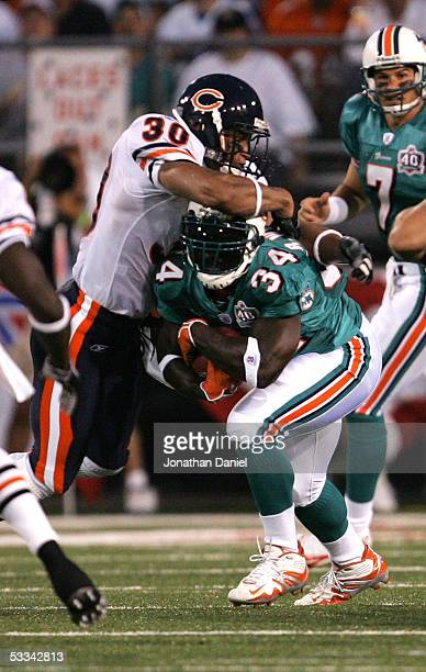 Running back Ricky Williams of the Miami Dolphins tries to break away from safety Mike Brown of the Chicago Bears during the NFL Hall of Fame...