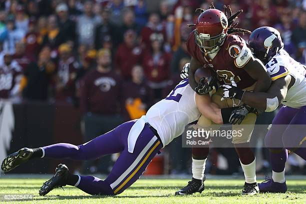Running back Rob Kelley of the Washington Redskins is tackled by free safety Harrison Smith and defensive tackle Shamar Stephen of the Minnesota...