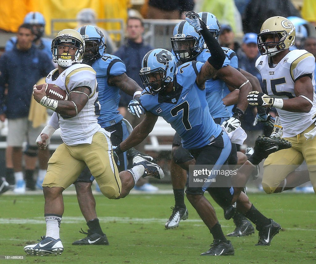 Running back Robert Godhigh #25 of the Georgia Tech Yellow Jackets is pursued by cornerback Tim Scott #7 of the North Carolina Tar Heels during the game at Bobby Dodd Stadium at Historic Grant Field on September 21, 2013 in Atlanta, Georgia.