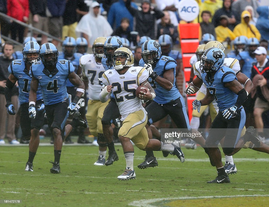 Running back Robert Godhigh #25 of the Georgia Tech Yellow Jackets is pursued by members of the North Carolina Tar Heels defense during the game at Bobby Dodd Stadium at Historic Grant Field on September 21, 2013 in Atlanta, Georgia.