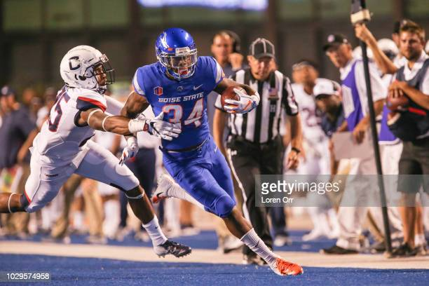 Running back Robert Mahone of the Boise State Broncos slips past the tackle attempt of defensive back Tyler Coyle of the Connecticut Huskies during...
