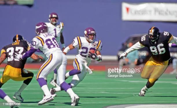 Running back Robert Smith of the Minnesota Vikings runs with football after taking a handoff from quarterback Warren Moon as he is pursued by...