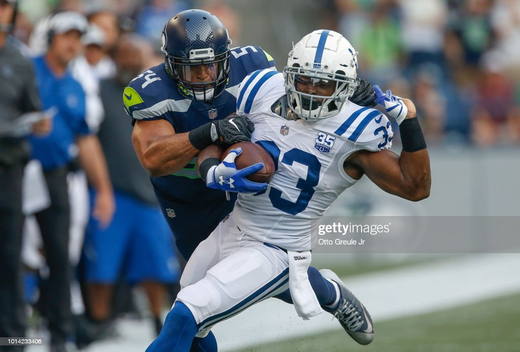 Running back Robert Turbin #33 of the Indianapolis Colts is tackled by middle linebacker Bobby Wagner #54 of the Seattle Seahawks at CenturyLink Field on August 9, 2018 in Seattle, Washington.