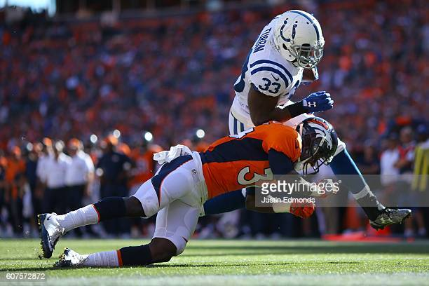 Running back Robert Turbin of the Indianapolis Colts runs in for a touchdown while defended by defensive back Will Parks of the Denver Broncos in the...