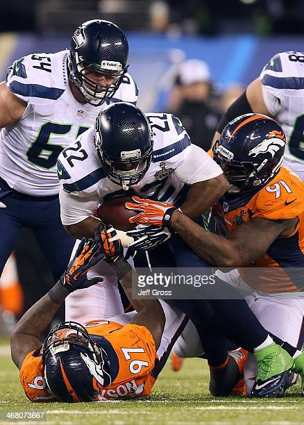 Running back Robert Turbin of the Seattle Seahawks is tackled by defensive end Malik Jackson and defensive end Robert Ayers of the Denver Broncos...