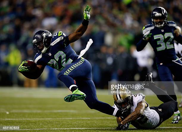 Running back Robert Turbin of the Seattle Seahawks is tackled by strong safety Kenny Vaccaro of the New Orleans Saints during a game at CenturyLink...