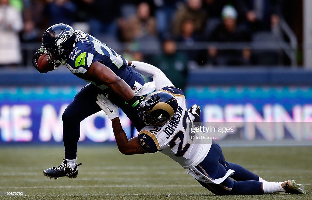 running back Robert Turbin #22 of the Seattle Seahawks is tackled by cornerback Trumaine Johnson #22 of the St. Louis Rams during the first quarter of the game at CenturyLink Field on December 28, 2014 in Seattle, Washington.