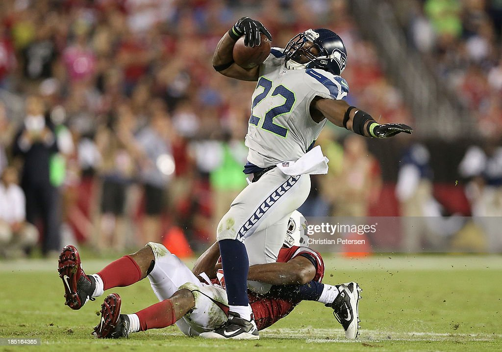 Running back Robert Turbin #22 of the Seattle Seahawks rushes the football against defensive end Darnell Dockett #90 of the Arizona Cardinals during the NFL game at the University of Phoenix Stadium on October 17, 2013 in Glendale, Arizona. The Seahawks defeated the Cardinals 34-22.