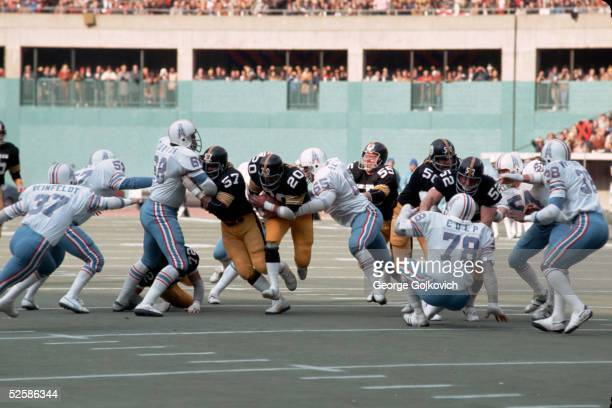 Running back Rocky Bleier of the Pittsburgh Steelers runs behind the blocking of offensive linemen Sam Davis Jon Kolb Jim Clack and Mike Webster as...