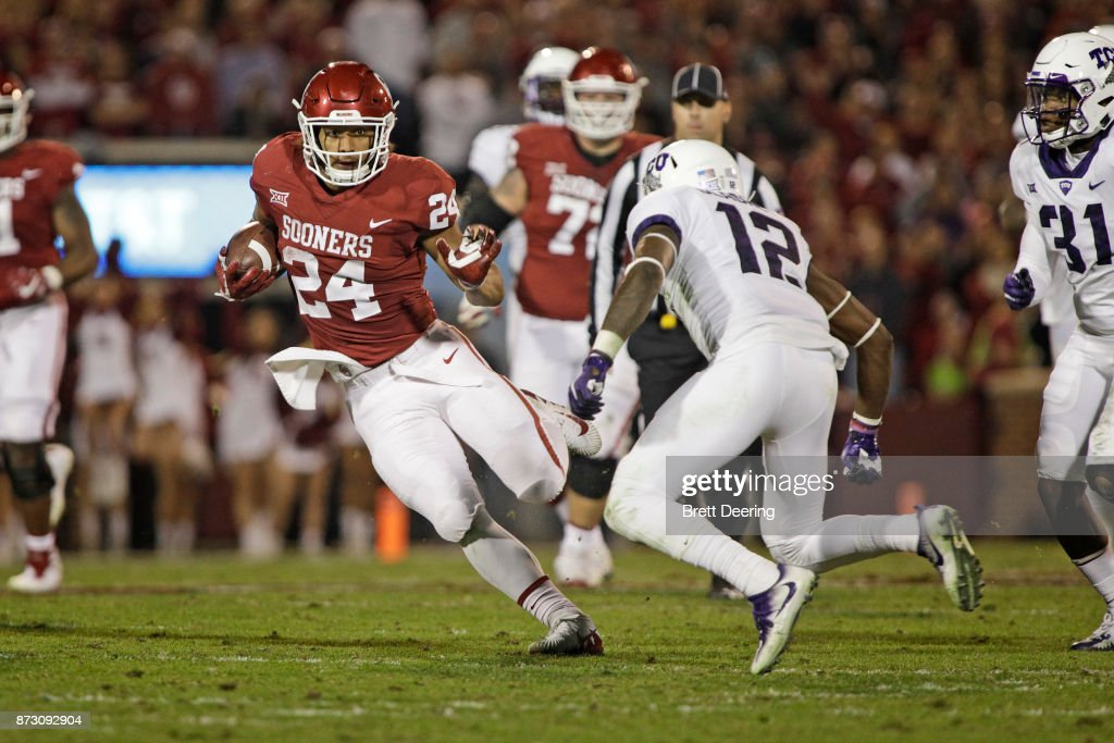 Running back Rodney Anderson #24 of the Oklahoma Sooners looks to get around cornerback Jeff Gladney #12 of the TCU Horned Frogs at Gaylord Family Oklahoma Memorial Stadium on November 11, 2017 in Norman, Oklahoma. Oklahoma defeated TCU