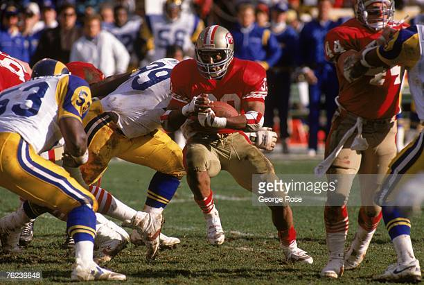 Running back Roger Craig of the San Francisco 49ers looks to make a move against Los Angeles Rams linebacker Fred Strickland during the 1989 NFC...