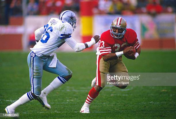 Running Back Roger Craig of the San Francisco 49ers looks to put a move on Michael Downs of the Dallas Cowboys during an NFL football game December...