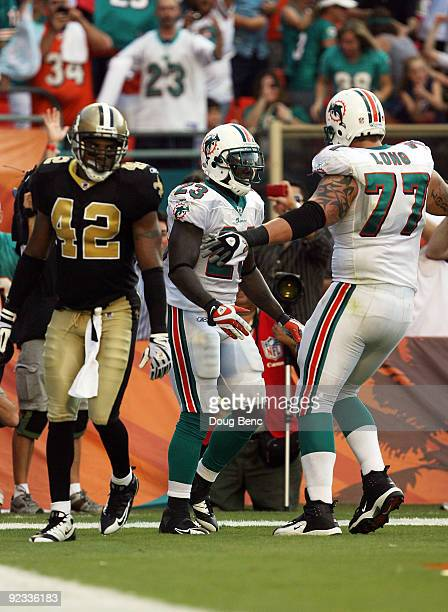 Running back Ronnie Brown of the Miami Dolphins celebrates his touchdown run with offensive tackle Jake Long as safety Darren Sharper of the New...
