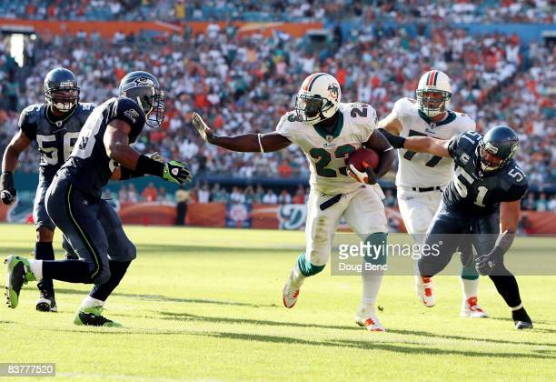 Running back Ronnie Brown of the Miami Dolphins scores a touchdown in the fourth quarter despite efforts by linebackers Julian Peterson and Lofa...