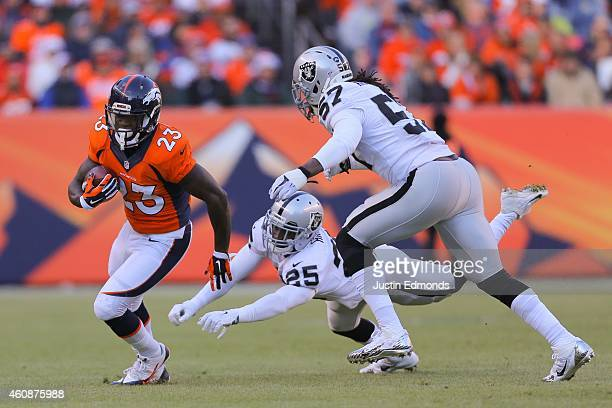 Running back Ronnie Hillman of the Denver Broncos avoids a tackle attempt by cornerback D.J. Hayden and outside linebacker Ray-Ray Armstrong of the...