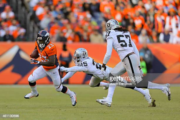 Running back Ronnie Hillman of the Denver Broncos runs with the football and eludes cornerback D.J. Hayden of the Oakland Raiders and outside...