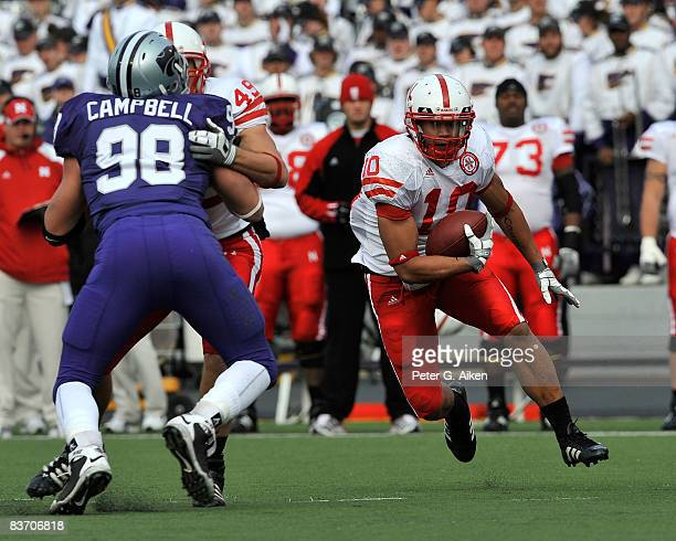 Running back Roy Helu Jr #10 of the Nebraska Cornhuskers gets blocking help from tightend Dreu Young on defensive end Ian Campbell of the Kansas...