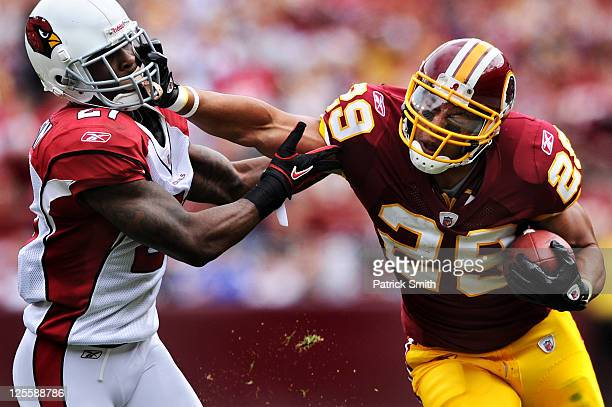 Running back Roy Helu of the Washington Redskins stiff arms corner back Patrick Peterson of the Arizona Cardinals during the second quarter at...