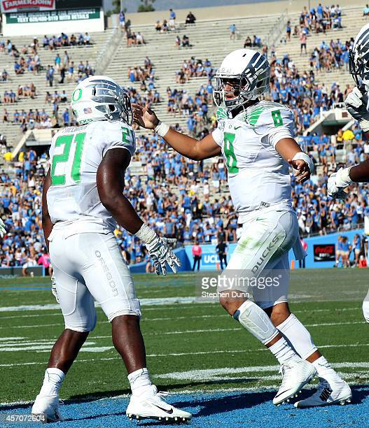 Running back Royce Freeman and quarterback Marcus Mariota of the Oregon Ducks carries celebrate Freeman's two yard run for a touchdown in the fourth...