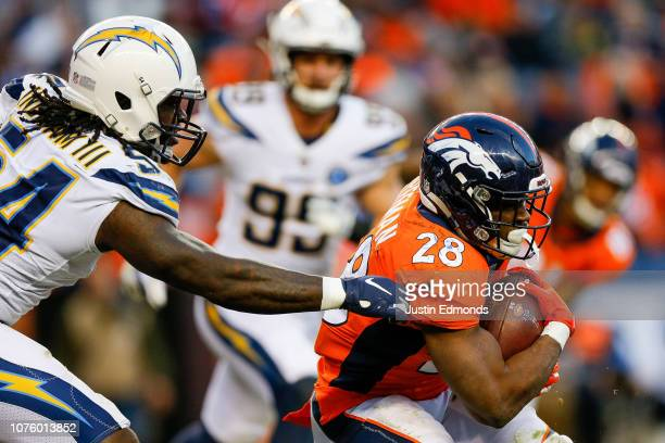 Running back Royce Freeman of the Denver Broncos carrels the ball and avoids a tackle attempt by defensive end Melvin Ingram of the Los Angeles...