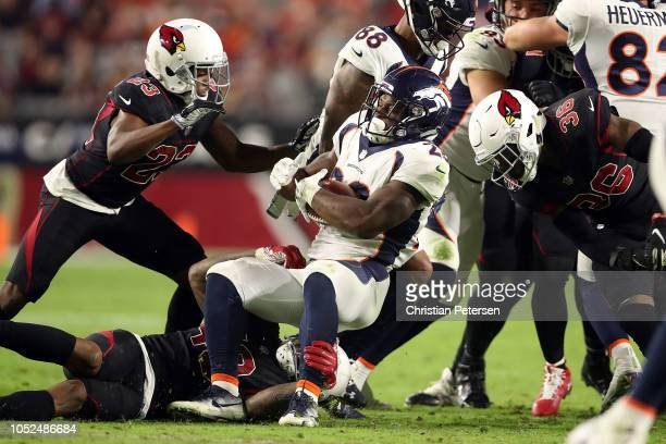 Running back Royce Freeman of the Denver Broncos is tackled by defensive back Bene' Benwikere linebacker Haason Reddick and strong safety Budda Baker...