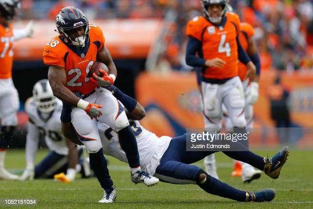 Running back Royce Freeman of the Denver Broncos is tackled by linebacker Mark Barron of the Los Angeles Rams during the second quarter at Broncos...