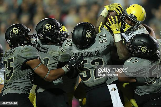 Running back Royce Freeman of the Oregon Ducks battles Leo Jackson III, Justin Solis and the Colorado Buffaloes defense as he rushes three yards for...
